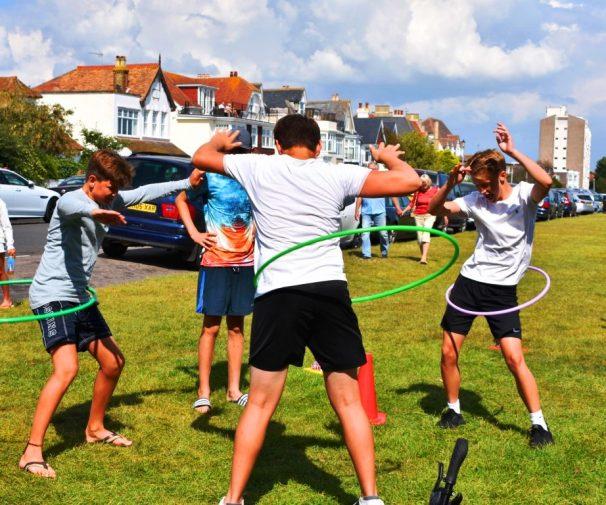 Teenage boys perform hula hoop exercise | Juliana Vandegrift