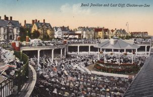 Tinted postcard of chairs with audience watching band perform on bandstand with covered roof | not known