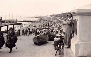 Black & white, young woman called Marjorie leaning against a wide pillar at entrance to Clacton beach beside pier (not in shot) | Not known
