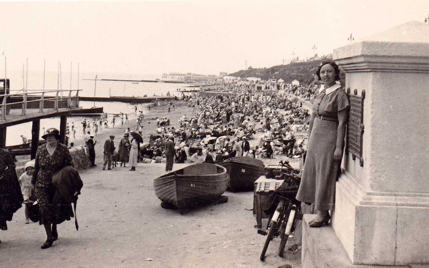 Black & white, young woman called Marjorie leaning against a wide pillar at entrance to Clacton beach beside pier (not in shot)