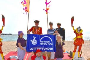 Colourful entertainers posing on beach with HLF poster