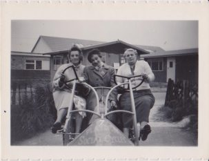 A wide four wheel bicycle for adults with two steering wheels and three women sitting across the seats looking alarmed!   Randall family member anon. (donated by daughter Barbara Birley)